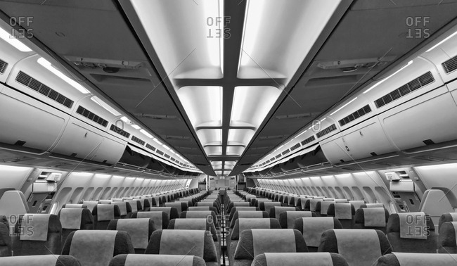 The interior of an airplane cabin with seats and headrests