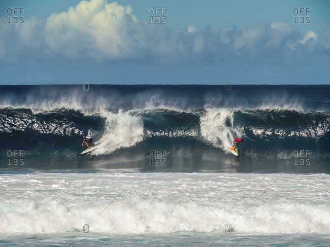 Two people surfing waves on the ocean