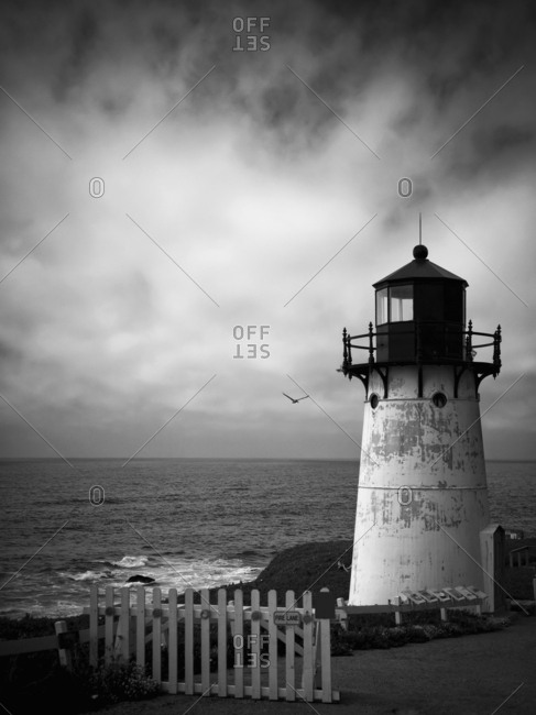 A lighthouse, a historic landmark on a rock shore and view out to sea