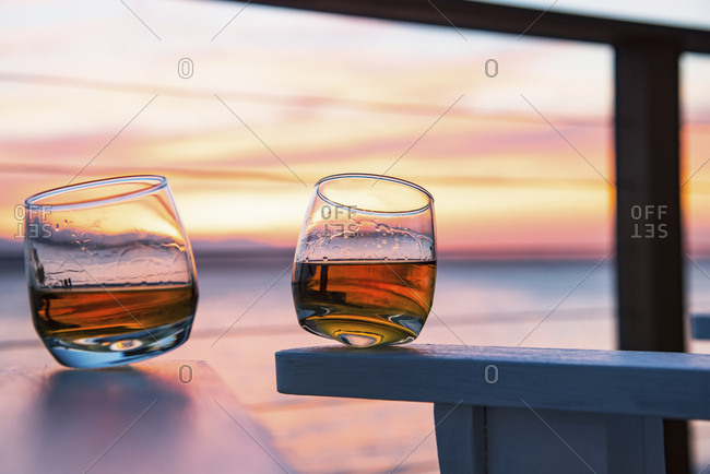 Two glasses of whisky against an ocean sunset