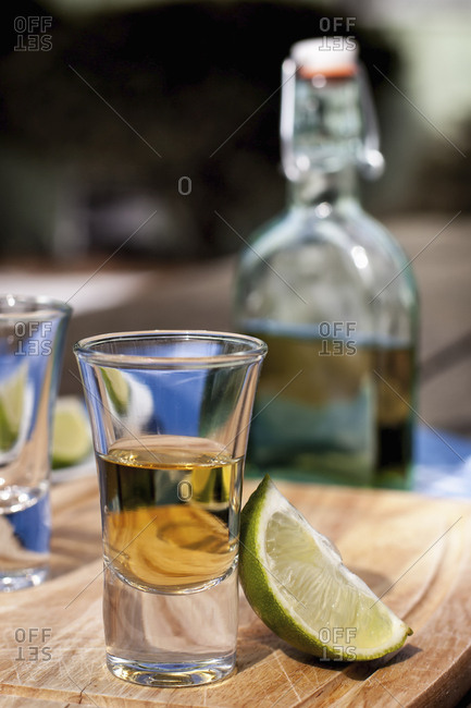 Shot glasses of tequila with lime wedges on a table with a bottle behind