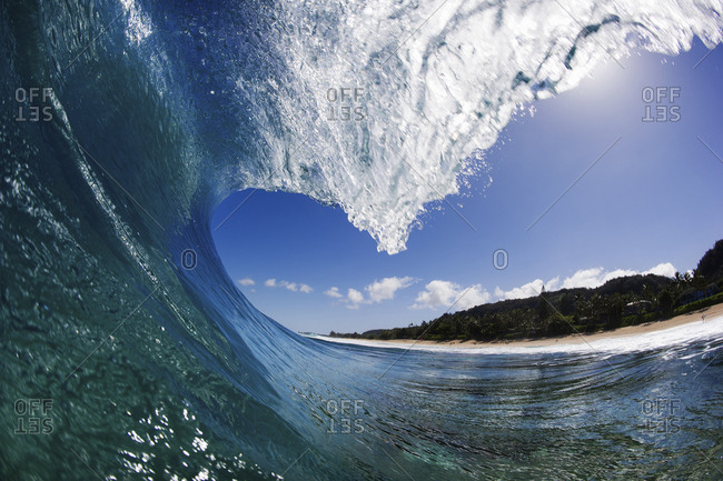 A wave tunnel with curling white water against a blue sky, just offshore