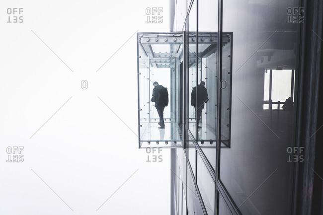 One person standing in a viewing box on the outside of a glass high-rise building