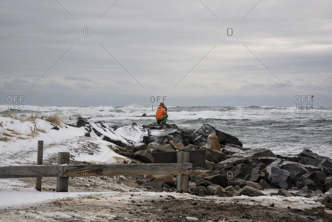 A person standing on a pile of rocks at the beach in winter