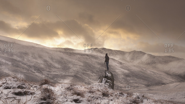 A person standing on a boulder in a snowy landscape