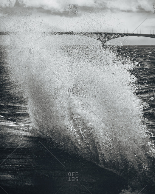 A wave washing over a wall in front of a bridge