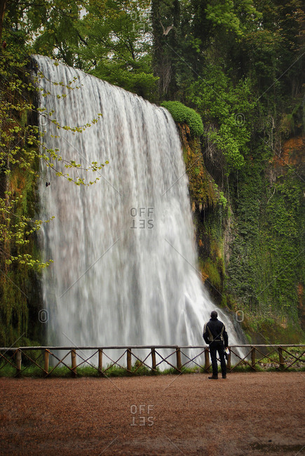 Rear view of one person looking at a waterfall