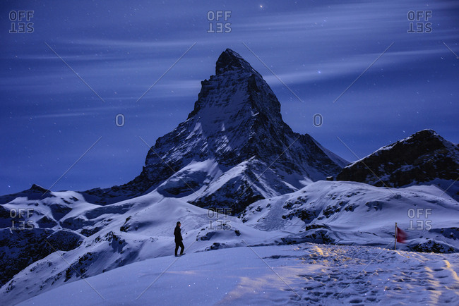 A person walking in a snowy mountainous landscape, with moonlight reflecting off the snow
