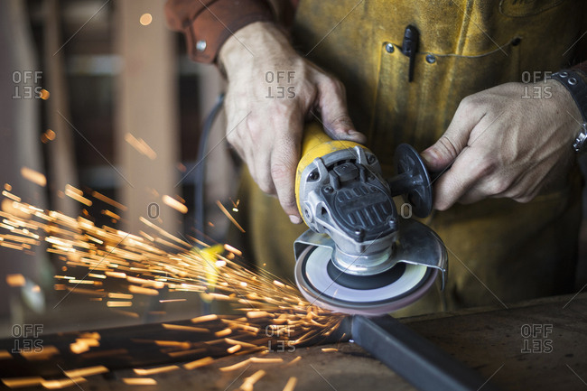 Close up of a metalworker using sander in a workshop making sparks fly