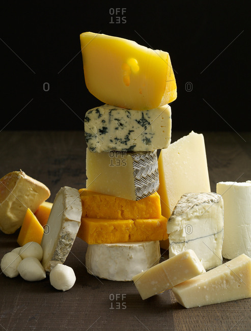 Variety of cheeses stacked on wooden surface