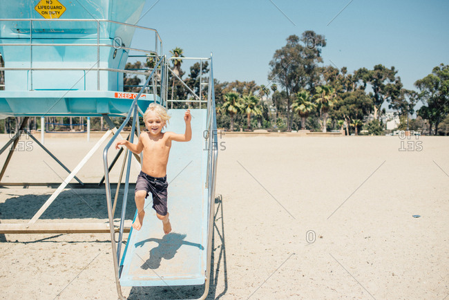 Young boy jumping off a ramp on a lifeguard tower