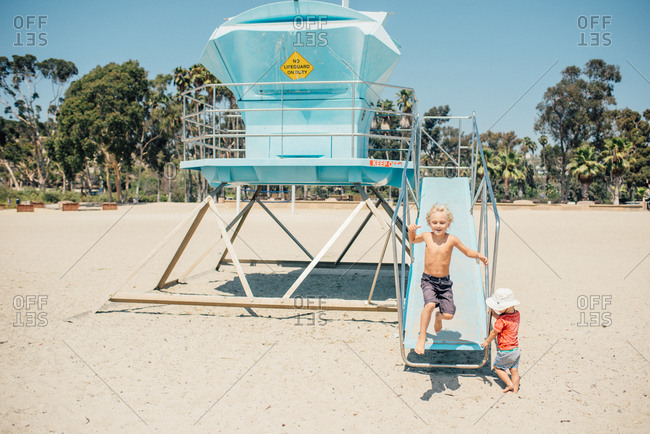 Two boys playing on a lifeguard tower at the beach