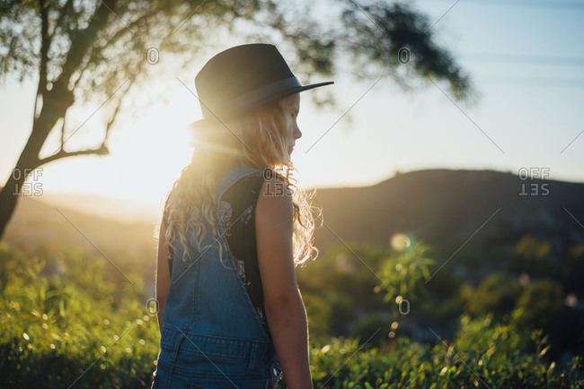 Young girl looking over the countryside at sunset