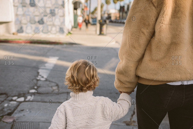 Mother and child crossing the street while holding hands