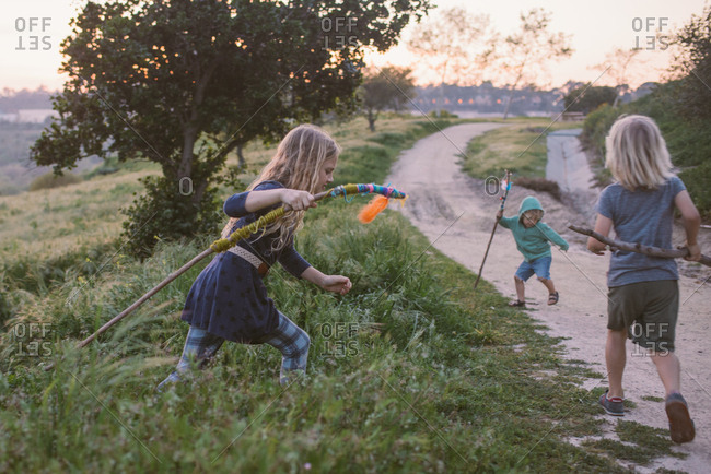 Kids playing in the countryside with decorated nature sticks