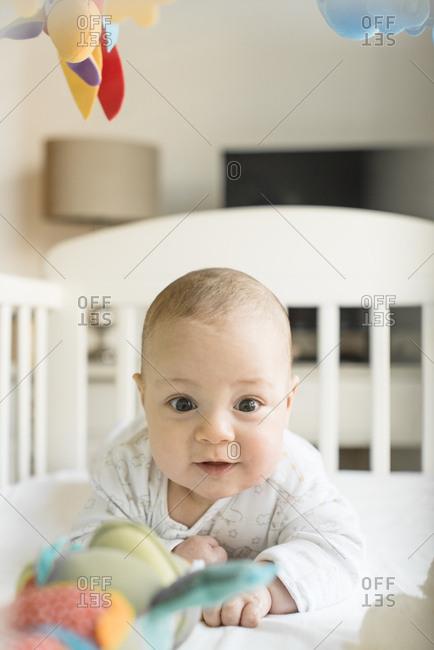 Happy baby lying on his tummy in crib
