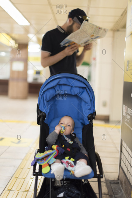 Baby waiting in stroller while father looks at a map