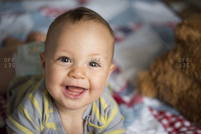 Smiling baby boy lying on a quilt