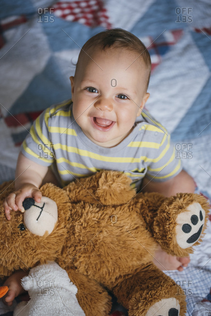 Smiling baby with stuffed animal