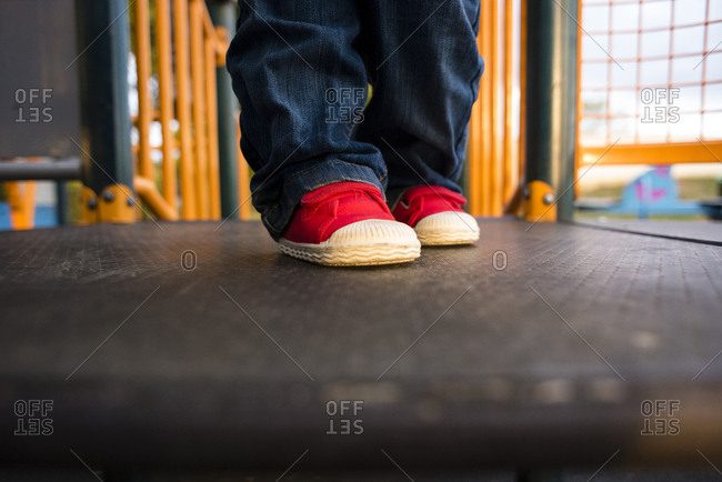 Legs of toddler wearing jeans and red shoes in a playground