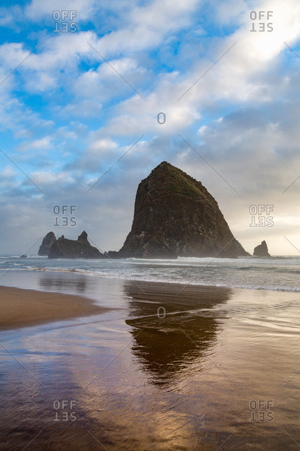 Haystack Rock reflected on the shoreline at Cannon Beach on the Pacific Northwest coast, Oregon, United States of America, North America