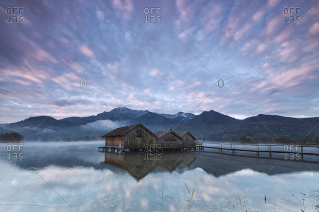 Pink clouds at sunset and wooden huts are reflected in the clear water of Kochelsee, Schlehdorf, Bavaria, Germany, Europe