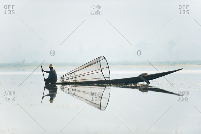 A basket fisherman on Inle Lake scans the still and shallow water for signs of life, Myanmar (Burma), Asia