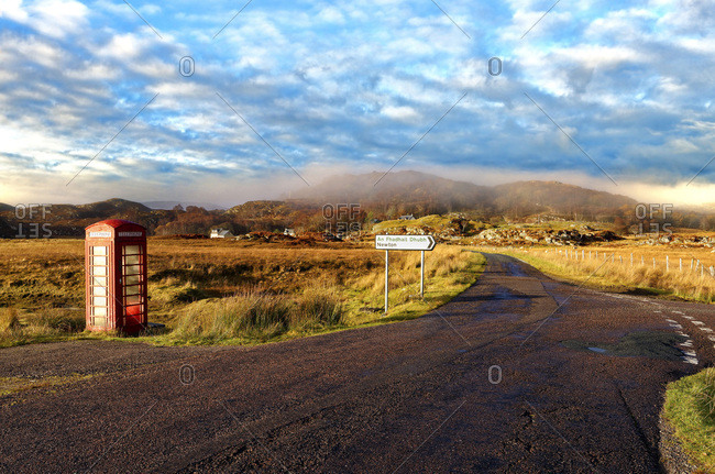 Autumn view of a red telephone box at the side of a quiet road in the remote misty Ardnamurchan moors of the Scottish Highlands, Scotland, United Kingdom, Europe
