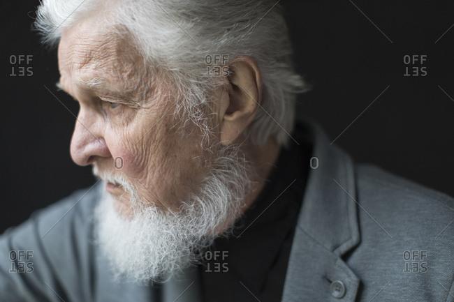 Close up of depressed senior man against black background