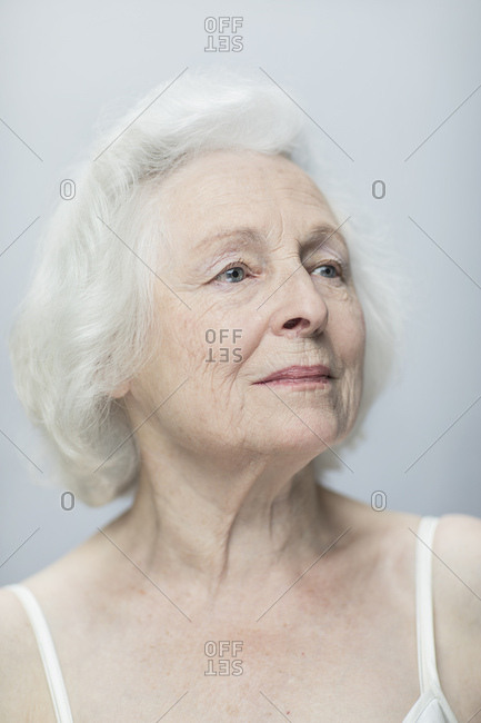 Close up of thoughtful senior woman against gray background