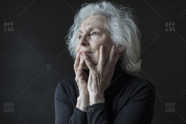 Close up of thoughtful senior woman with hands on face against black background