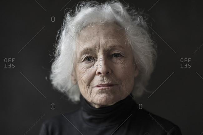 Close up portrait of confident senior woman over black background
