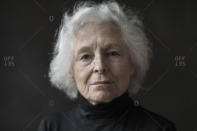 Close up portrait of confident senior woman over black background