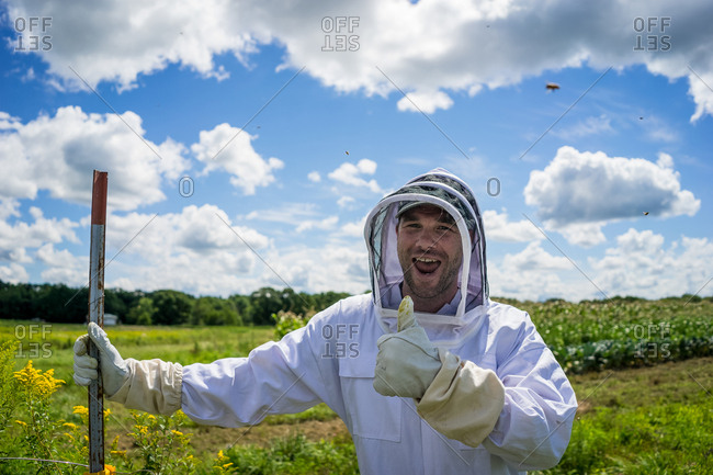 Man in beekeeper suit out in field