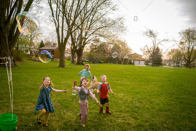 Young children playing with giant bubbles on a summer evening