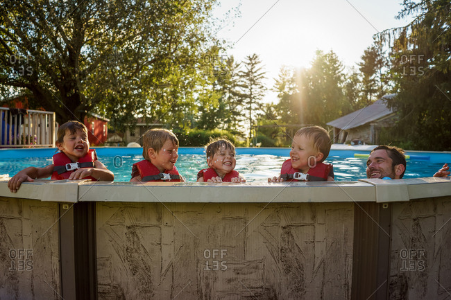 Four children in life jackets on the edge of a swimming pool