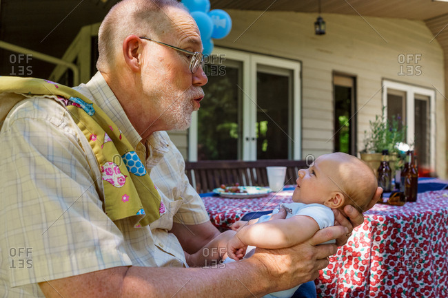 Grandfather holding new grandchild - Offset