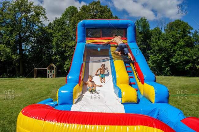 boys playing on inflatable water slide