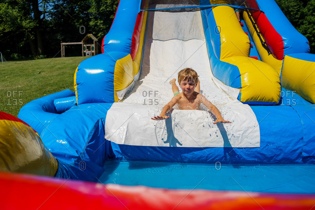 boy playing on inflatable water slide