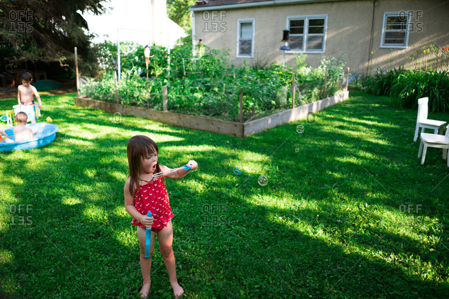 Young girl in backyard blowing bubbles