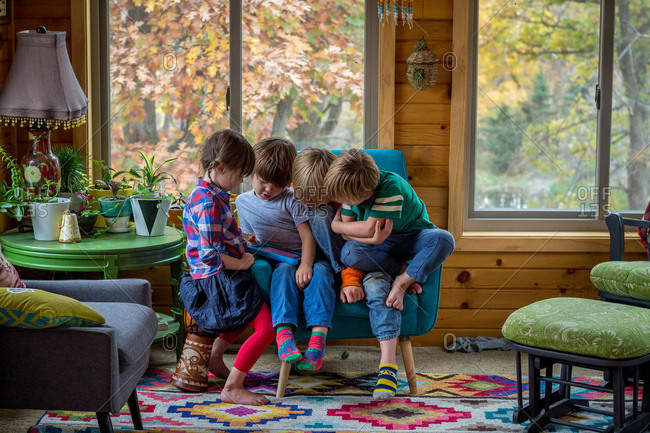 Four young children watching video pad together
