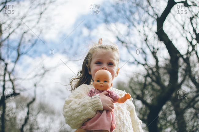 Low angle view of toddler girl holding her doll