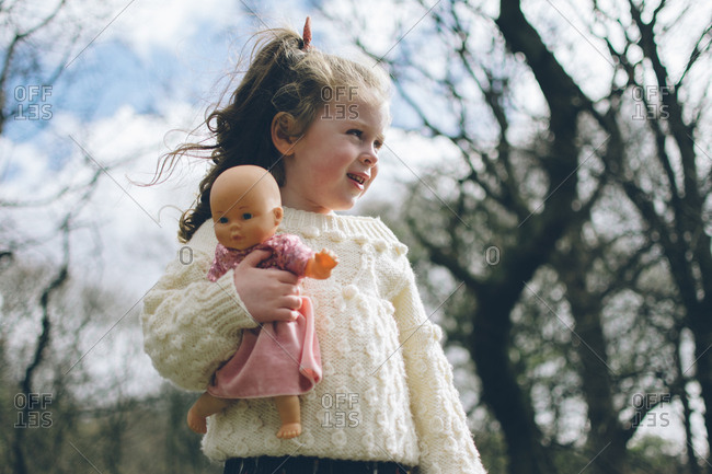Toddler girl in white sweater holding doll outdoors