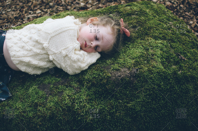 Young girl lying on a mossy rock