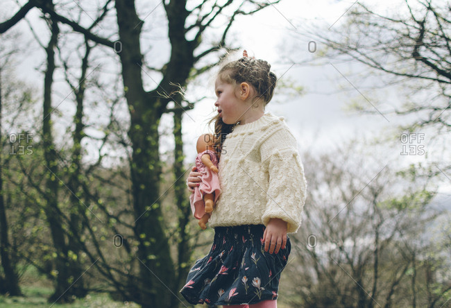 Girl with doll outdoors in spring