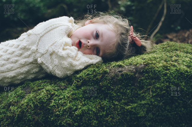 Close-up portrait of toddler girl lying on a mossy rock