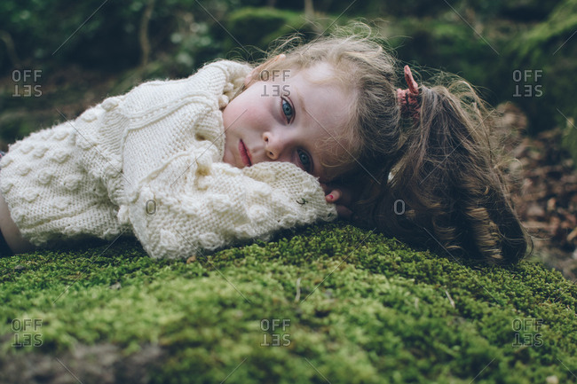 Portrait of a beautiful young girl lying on mossy rock