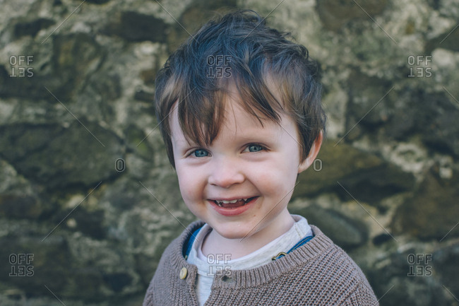 Portrait of toddler boy in front of rock wall