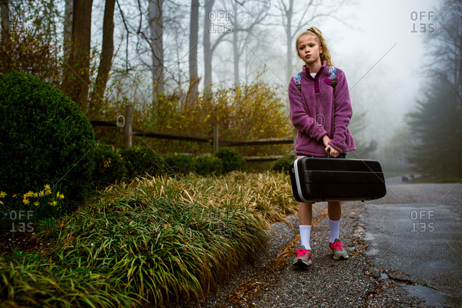 Girl standing outside with instrument case