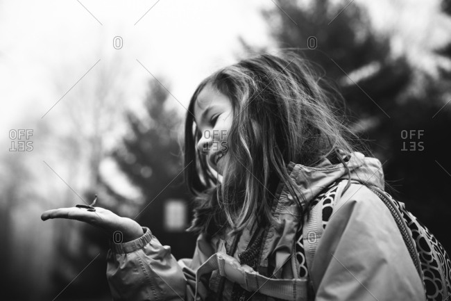 Young girl smiling at earthworm in palm